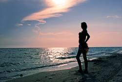 Teenage girl on the sea beach at sunset