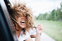 Happy woman with curly hair riding in car laughing