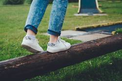 Girl balancing on a log in white canvas shoes.