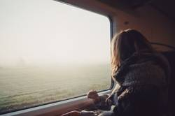 Girl in a train looking an idyllic landscape in a foggy morning.