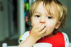 portrait adorable child eating chocolate sponge cake