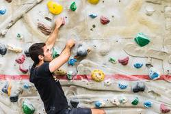 Man practicing rock climbing on artificial wall indoors.