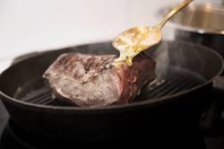 Sauce über ein Steak in einer Pfanne