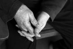 Seniorenhände in Schwarz-Weiß neben Stuhllehne