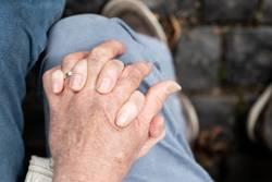 Zwei Hände auf einem Knie