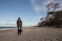 Woman walking the dog at the baltic sea.