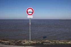 Wellen-Warnschild am Strand.