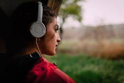 Girl listening music in her shelter hut with headphones