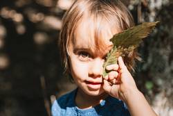 Portrait of little girl with leaf in her face in the forest
