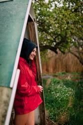Smiling girl with red raincoat takes shelter from the rain