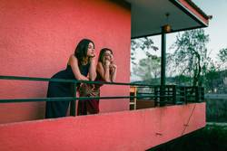 Two young women watch the sunset from their balcony.