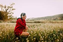 Girl listening music with headphones sitting among wildflowers