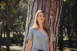 Young smiling blonde woman wearing a grey t-shirt in the park