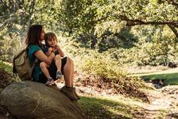 Mother and daughter seating embraced on a stone in the forest