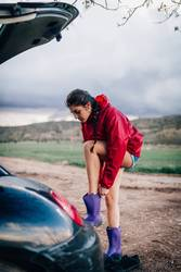 Girl putting her waterproof boots near her car.