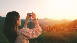 Young asian woman taking photo with her smartphone