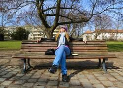 Frau genießt Sonne auf Parkbank