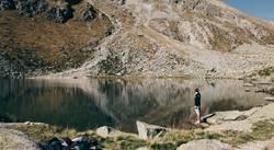 Junger Mann vor Gebirgssee in Südtirol | E5 Alpenüberquerung