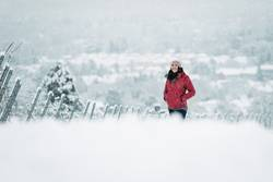 Frau mit roter Jacke in verschneiter Winterlandschaft