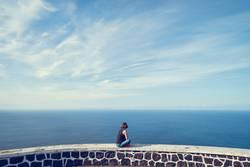 Junge Frau guckt auf Meer und Himmel auf den Azoren