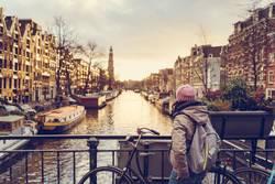 Frau guckt bei Sonnenuntergang auf einen der Kanäle im Amsterdam