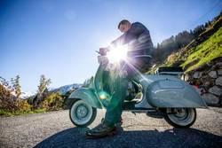Oldtimer Vespa Motorroller fahren im Sommer