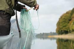 Fischer auf Fischerboot am See legt Fischernetz aus