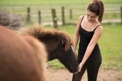 Junge Frau mit Pferdeschwanz auf Pferdekoppel bei den Pferden