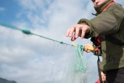 Junger Fischer holt Fischernetz ein