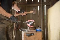 Hufschmied produziert mit dem Hammer ein Hufeisen am Amboss