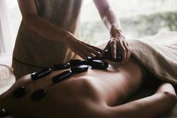 Back massage with oil and hot stones