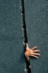 Hand durch engen Spalt in Steinwand