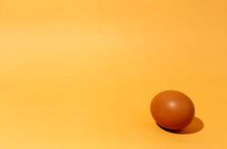Fresh raw eggs on brown background