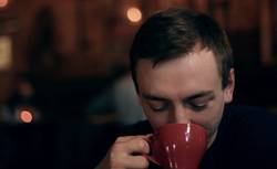 Handsome young caucasian male drinking from a red cup
