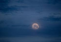 Großer roter Mond am blauen leicht bewölkten Abendhimmel