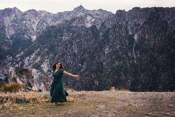 Portrait of a happy woman dancing barefoot on the mountain
