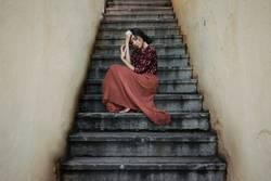 Portrait of melancholic woman sitting on symmetrical staircase