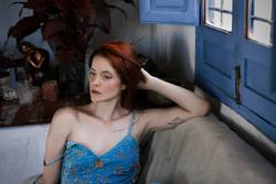 Portrait of sensual redhead woman sitting on sofa and thoughtful