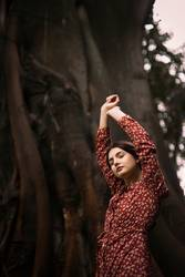 Young woman with raised arms in front of a tree trunk