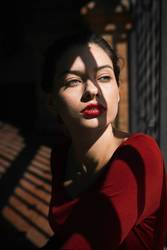 Portrait of pretty woman with red lips and shadow on her face