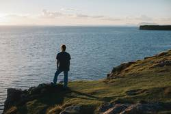 Portrait of back man looking out to sea from a cliff at sunset