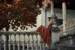 Barefoot woman sitting on railing of an old palace