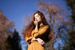 Autumnal portrait of redhead woman in the sun touching her face