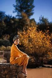 Autumnal portrait of mulatto barefoot woman sitting on stone