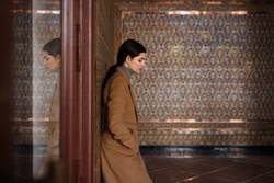 Frau mit dem Mantel, der auf Fliesenwand stillsteht und in einem Glas reflektiert ist