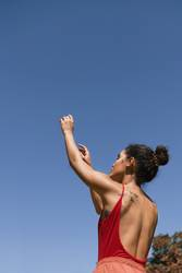 Young woman with back to the air and with arms raised to the sky