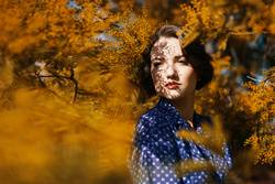 Woman surrounded by a Mimosa tree with shadows on her face