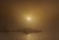 Sunrise over small rocky island on a foggy day
