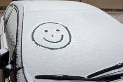 smiley graffiti on windshield in new snow