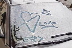 heart love graffiti on car windshield in new snow